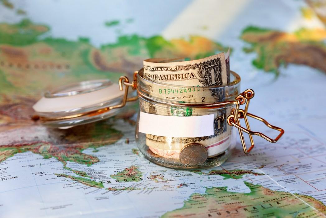 Glas mit US Dollar steht auf einer Weltkarte