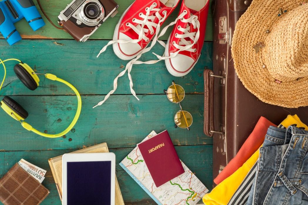 Sonnenhut, Schuhe, Sonnenbrille, Koffer, Fernglas, Kleidung und ein Kopfhörer liegen auf dem Boden