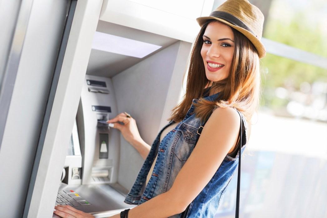 Frau hebt Geld auf ihrer Weltreise am Automaten ab