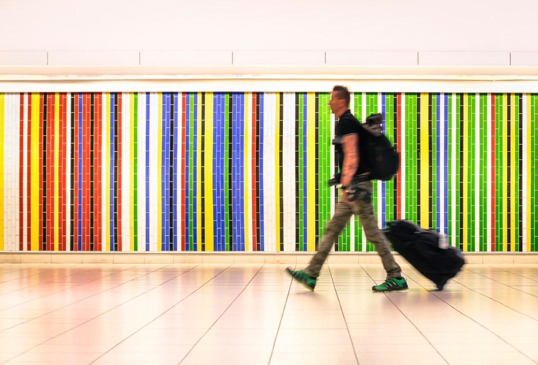 Mann zieht einen Koffer durch den Flughafen