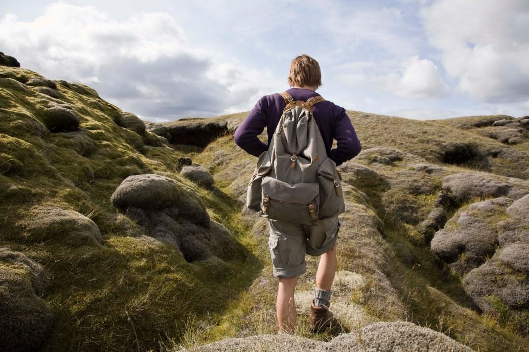 Mensch mit Rucksack wandert über einen Berg
