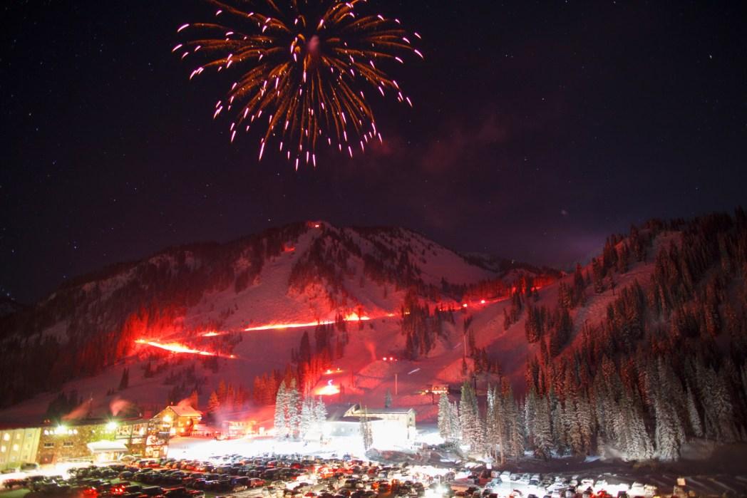 Beleuchtete Nachtpiste samt Silvester-Feuerwerk und Skifahrer